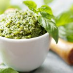 Closeup of freshly made Basil pesto in ramekin with background of fresh basil out of focus
