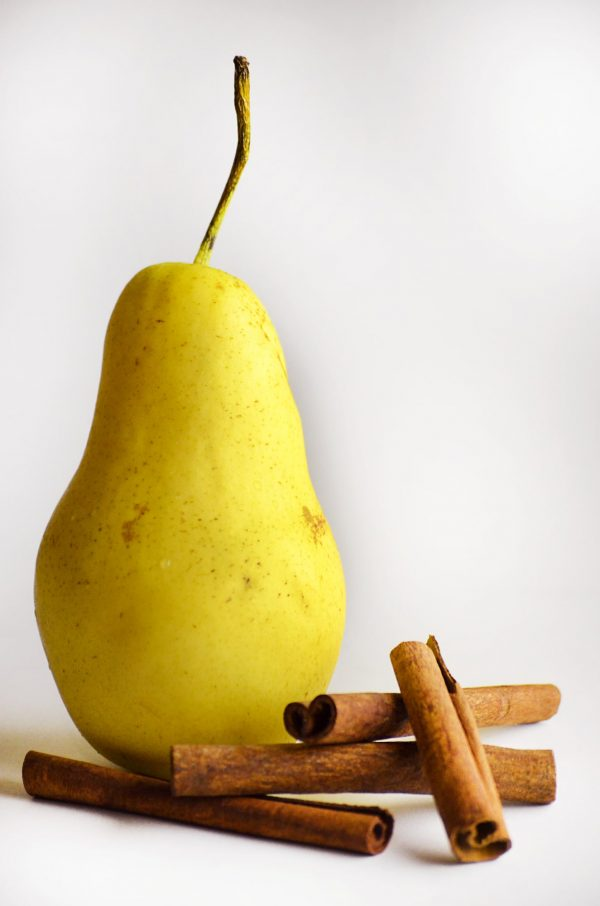 yellow pear and cinnamon sticks on white background
