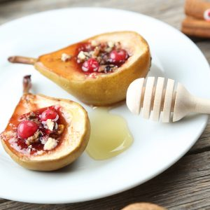 Cutlivated Tree Olive Oil Baked pears with honey, walnuts and cranberries on grey wooden table