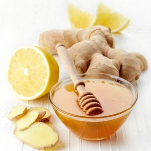 Fresh ginger root, honey and lemon on white wooden background