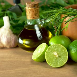 Limes on board with oil bottle, garlic bulbs and fresh herbs