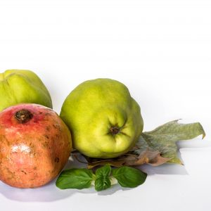 Fresh quinces and pomegranates isolated on white background