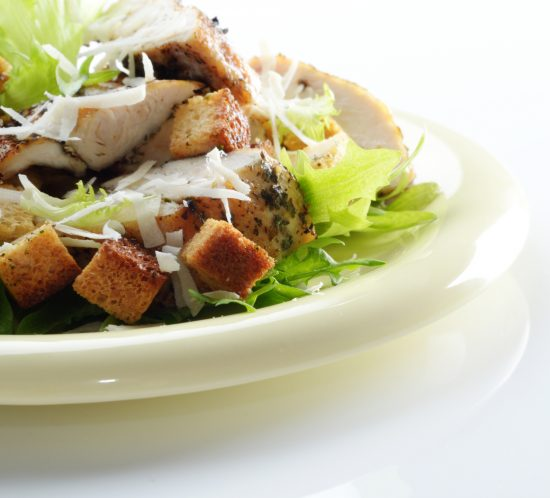 Caesar chicken salad with grated parmesan on white background