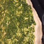Pizza dough on Emile Henry Pizza Stone with pesto